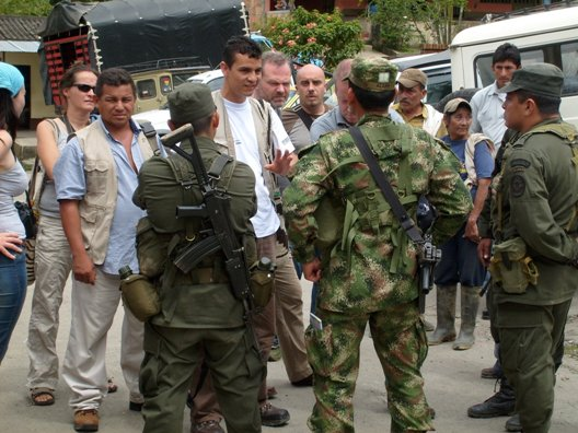 Colombian and solidarity activists talk with armed Colombian military personnel